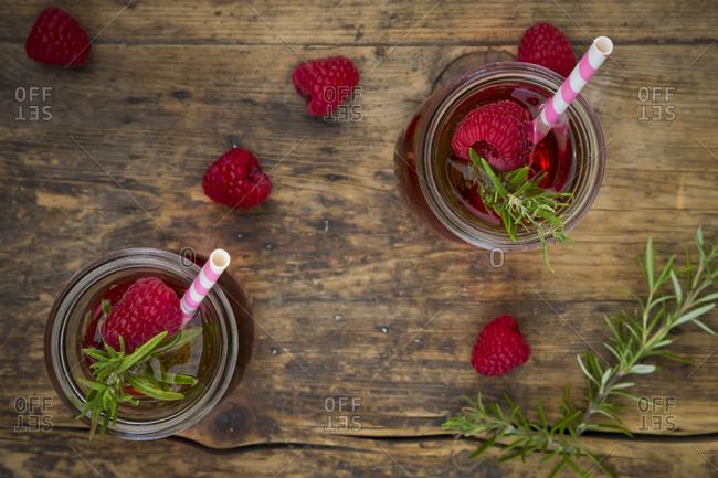 Two glass bottles of homemade raspberry lemonade flavored with rosemary