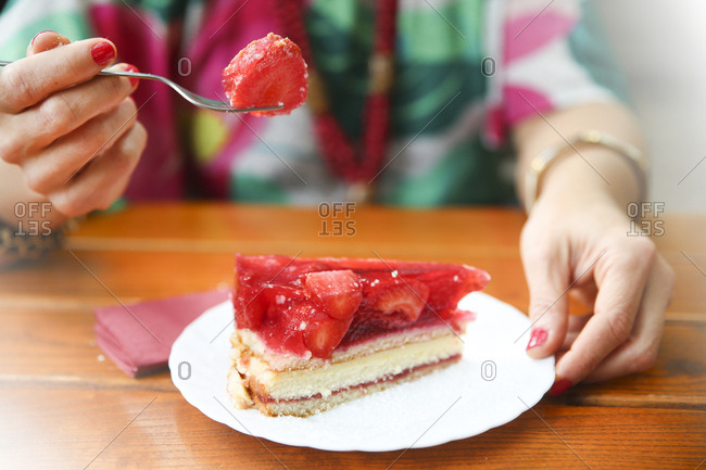 Close-up of woman eating strawberry cake in street cafe