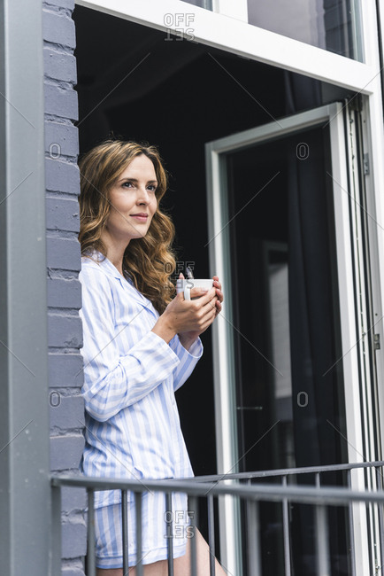 Smiling woman in pajama at home with cup of coffee looking out of balcony door