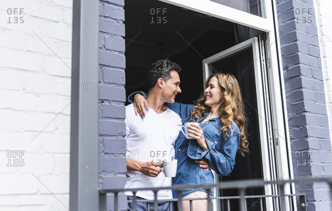 Smiling couple in nightwear at home with cups of coffee at balcony door