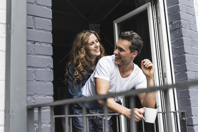 Happy couple in nightwear at home at balcony door