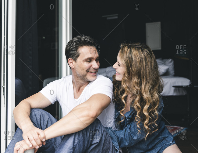 Happy couple in nightwear at home sitting at French window