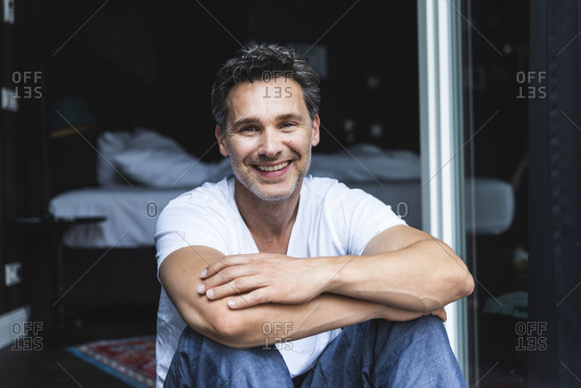 Portrait of smiling man in pajama at home sitting at French window