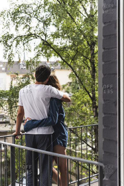 Rear view of couple in nightwear standing on balcony hugging