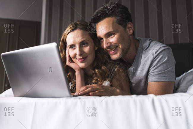 Smiling couple lying on bed at home looking at laptop