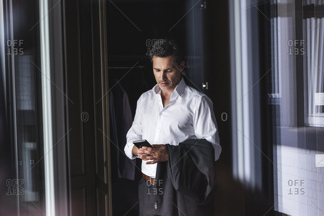 Businessman standing at wardrobe at home using cell phone