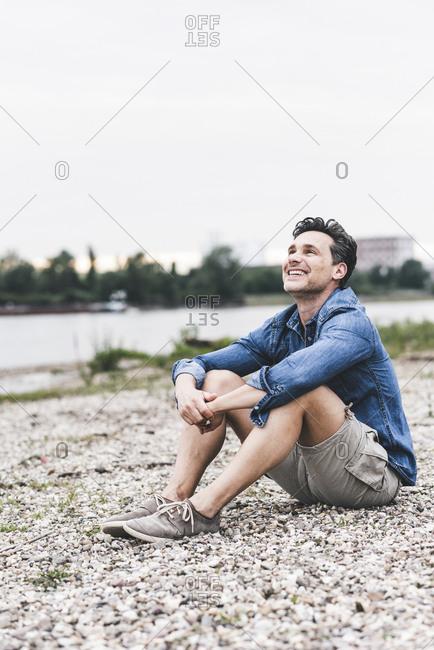 Smiling man sitting at the riverside looking up