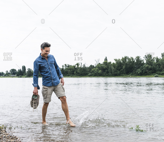 Smiling man splashing water in a river