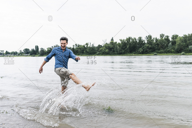 Laughing man splashing water in a river