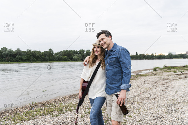 Happy couple walking at the riverside with beer bottle and guitar