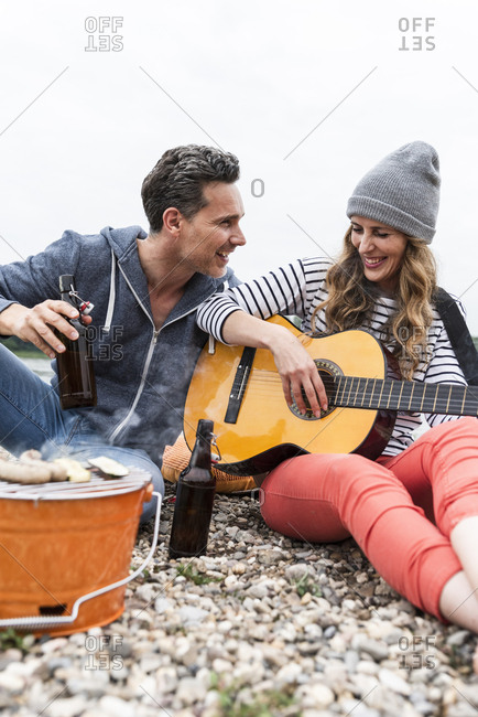 Happy couple with beer bottles- guitar and grill relaxing on pebble beach