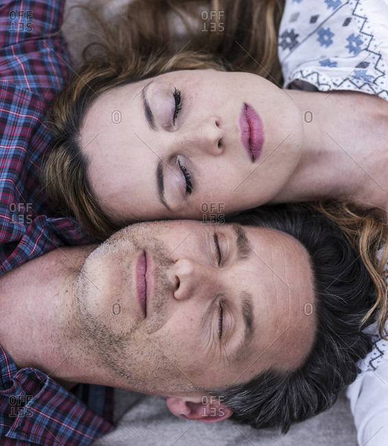 Couple with closed eyes lying down head to head