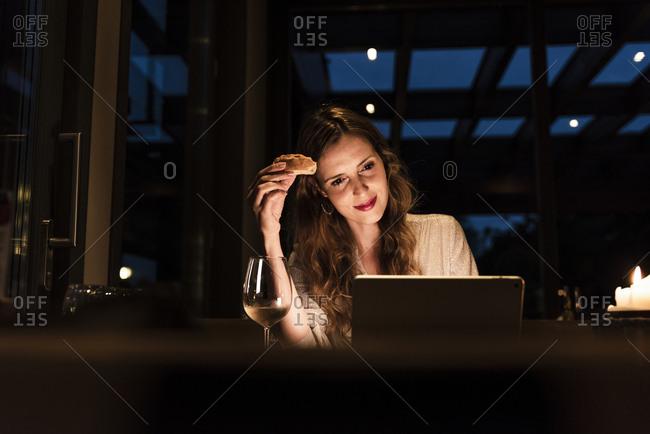 Smiling woman having dinner looking at laptop