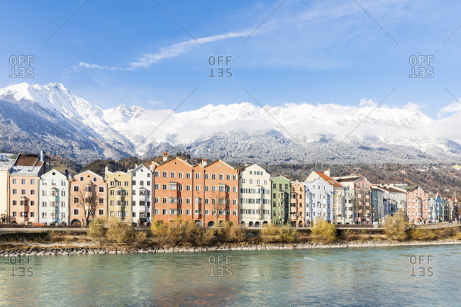 Austria- Innsbruck- row of houses in front of Nordkette Mountains with Inn River in the foreground