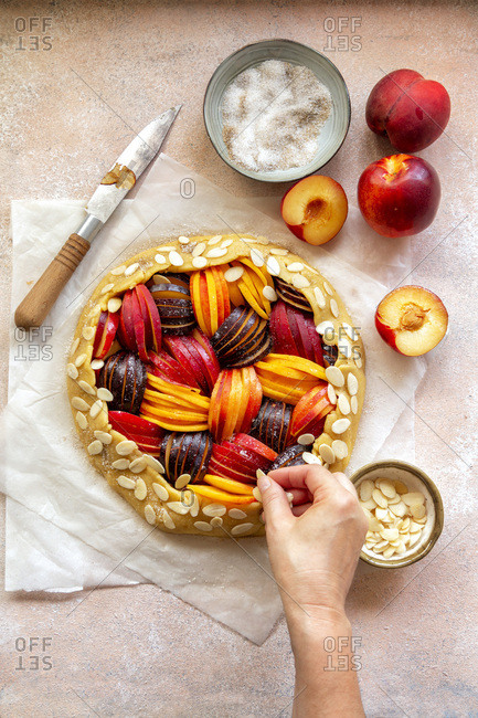 Preparing a stone fruit galette Hand sprinkles almond flakes over the crust