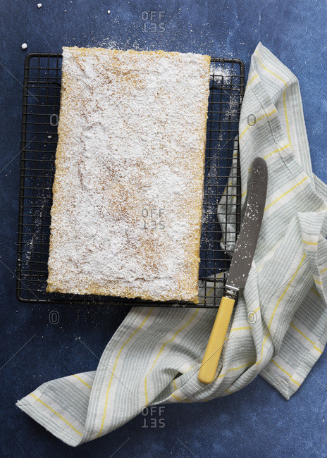 Lemon slice on a cake rack with a knife