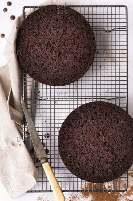 Round chocolate cake cut in two halves cooling on a wire cake rack