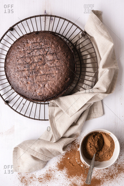 Round home baked chocolate cake cooling on a wire cake rack