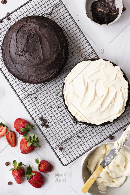 Round chocolate cake on a cake rack covered with chocolate icing and filled with cream