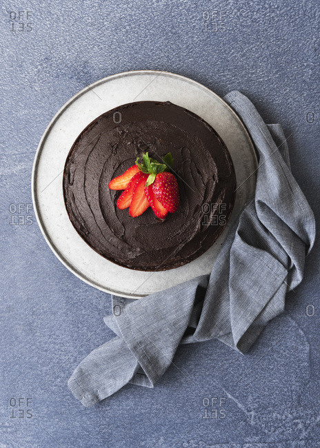 Chocolate dessert cake with chocolate icing and a sliced strawberry on top