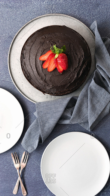 Round gluten-free chocolate cake with two plates and two cake forks