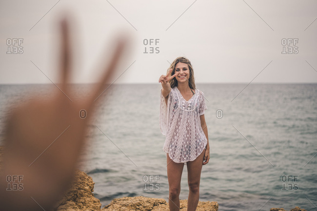 Portrait of happy young woman standing on a rock at the sea making peace sign