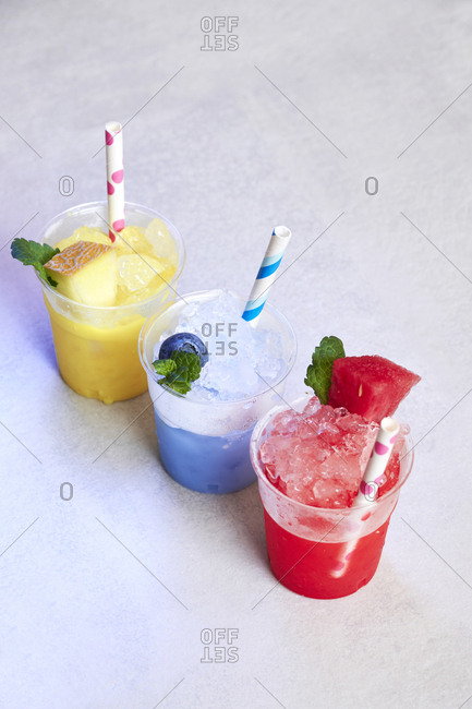 Row of three plastic cups of various fruit slushes