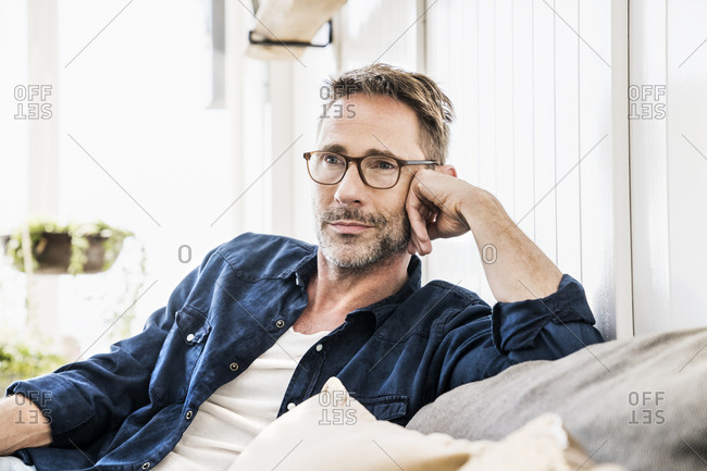 Man wearing glasses relaxing on couch