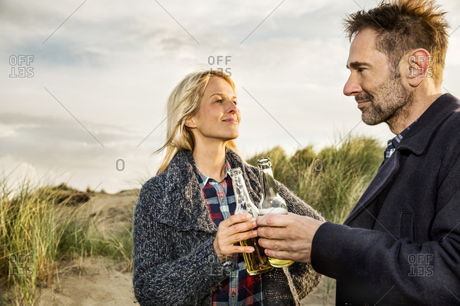 Smiling couple in dunes clinking beer bottles