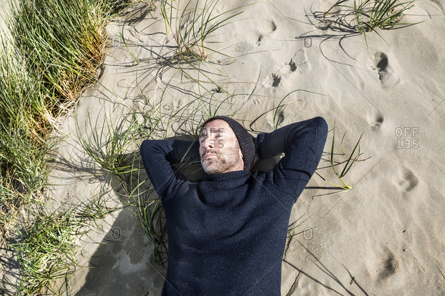 Man wearing woolly hat lying in beach dune