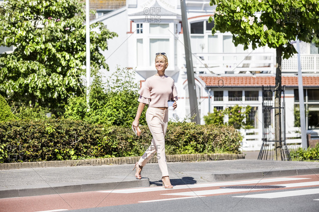 Smiling woman crossing a street