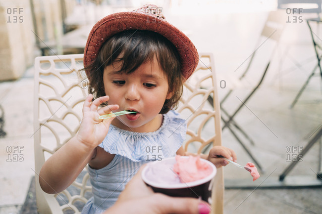 Cute toddler girl eating an ice cream held by her mother