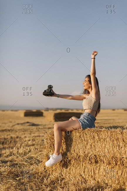 Young woman sitting on straw bale taking selfie with instant camera