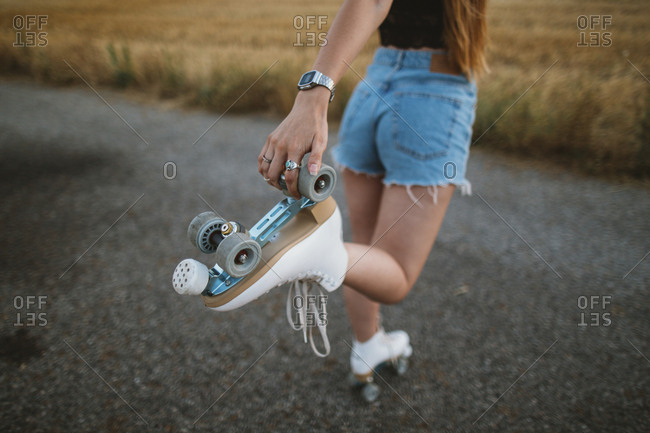 Young woman with roller skates on country road- partial view