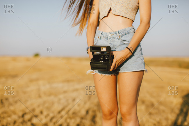 Young woman with instant camera on a field at sunset- partial view