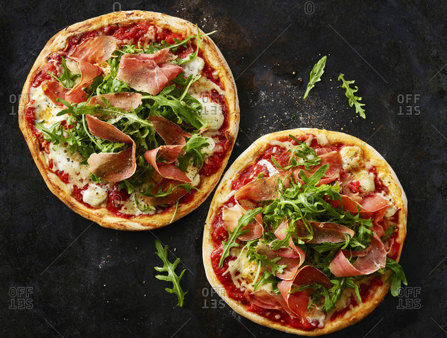 Pizza with ham and rocket on dark ground