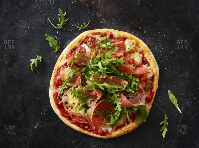 Pizza with ham and rocket on dark ground