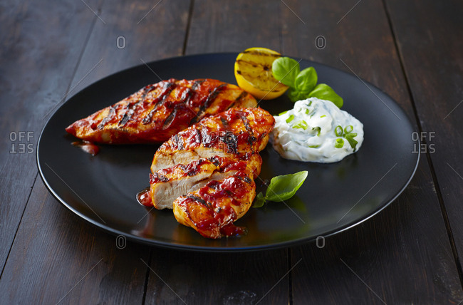 Grilled chicken breast fillet with sour cream on plate