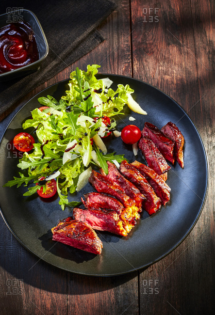 Beefsteak with lettuce dish on plate