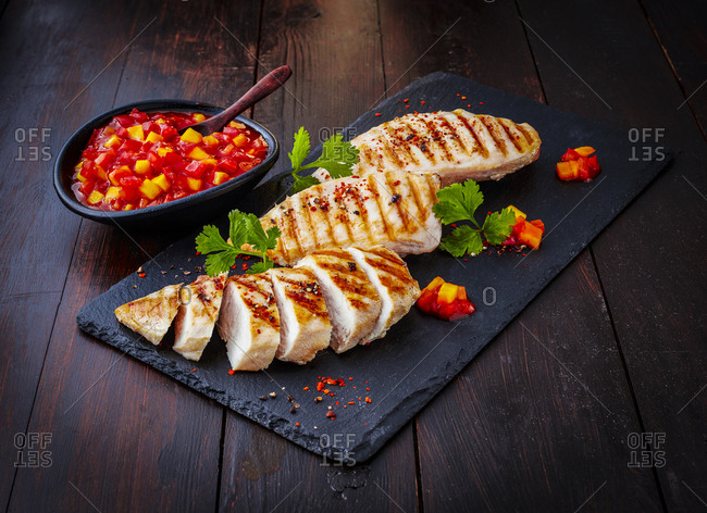 Chicken breast fillet with bell pepper chutney on slate