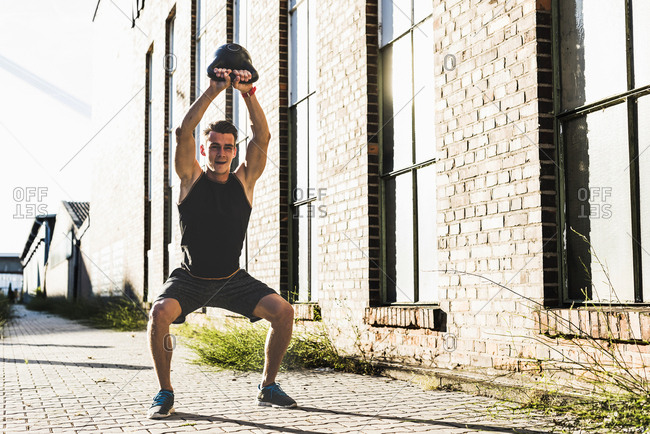 Young man training with a kettle bell