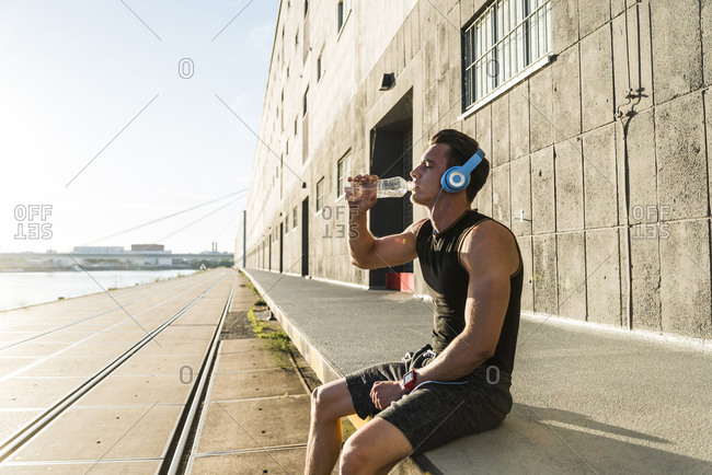 Young athlete wearing headphones- sitting on a wall