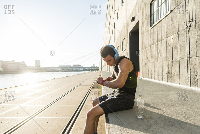 Young athlete wearing headphones- sitting on a wall- checking smartwatch
