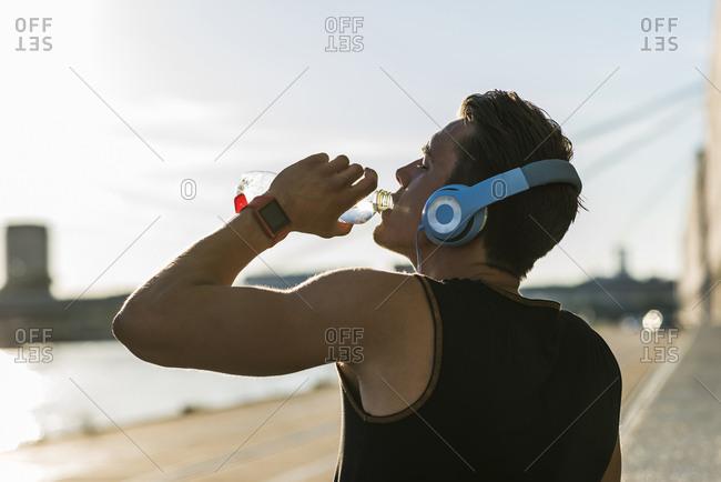Young man wearing headphones- drinking water