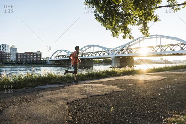 Young man dribbling basketball at the river