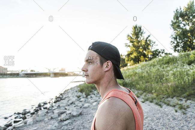 Young man wearing baseball cap looking at the river