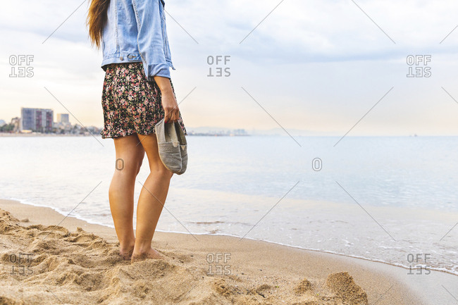 Spain- Barcelona- woman standing barefoot on the beach