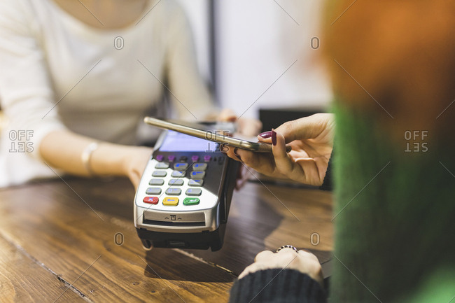 Customer paying cashless with smartphone in a shop