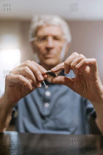 Senior man examining hearing aid