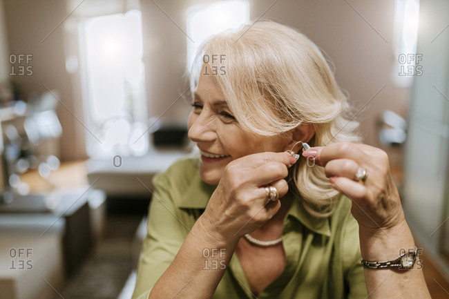 Senior woman applying hearing aid
